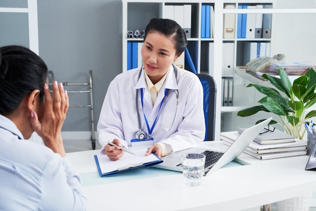 General practitioner taking notes when talking to female patient suffering from severe headache