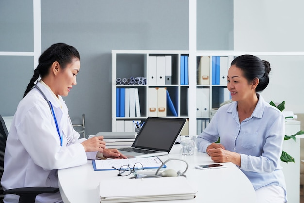 一般開業医が高齢の患者と話し、彼女の個人データと苦情をフォームに記入する