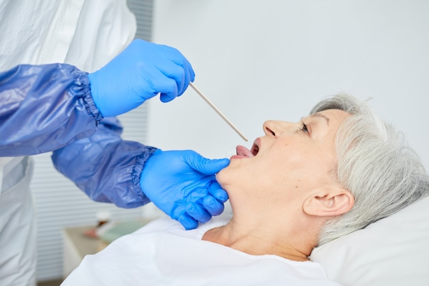 General practitioner waring latex gloves examining senior patient's throat