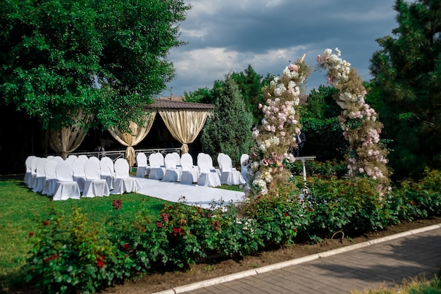 General view of the decoration of the wedding ceremony in the garden in the air. wedding decor an arch made of fresh flowers, chairs in covers for guests