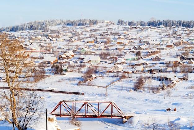 Общий вид русской деревни на склоне холма в солнечный морозный зимний день