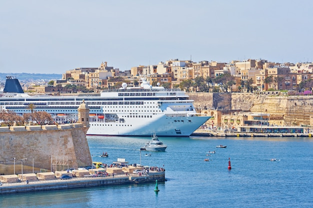 General view of valletta grand harbor in malta with large cruise liner ship in sea bay.