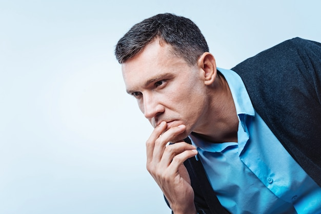 Генерация идей. на снимке в профиль вдумчивый мужчина, который касается рта, смотрит в пустоту и думает о чем-то на заднем плане.