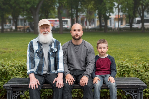 Generations of men are sitting in a park on a bench