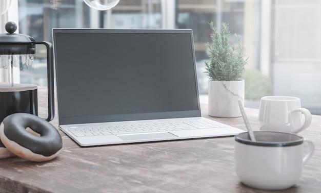 一般的なラップトップコンピューターと木製のテーブルで休むコーヒーカップ。モックアップの空白の画面