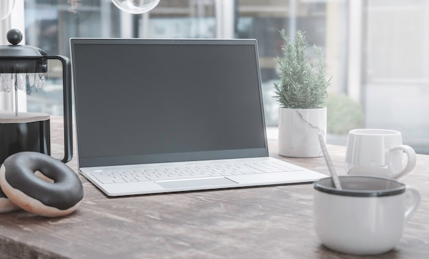 Generic laptop computer and coffee cup resting on wooden table. blank screen for mockup
