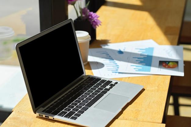 Универсальный портативный компьютер с черным экраном и отчетными документами на деревянном столе у окна