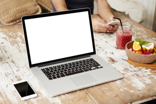 携帯電話、スムージー、フルーツの木製テーブルで休んでいる空白のコピースペース画面で汎用のモダンなノートパソコン。