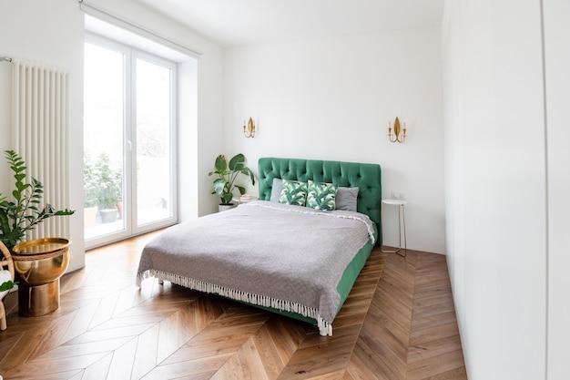 Большая двухместная спальня с большими окнами и высокими потолками.