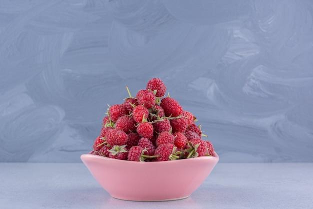 Щедрая порция малины в розовой миске на мраморном фоне. фото высокого качества