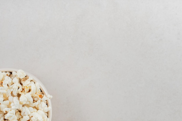 Generous serving of popcorn in a white bowl on marble table.