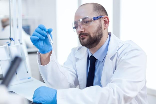 Генетик, проводящий фармакологические эксперименты, исследователь в стерильной лаборатории биотехнологии, проводящий анализ в пробирке в перчатках и защитных очках.