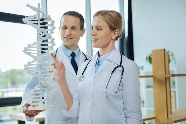 유전 연구. 미소하고 그녀의 동료와 함께 서있는 동안 dna 모델을 가리키는 행복 긍정적 인 여성 과학자