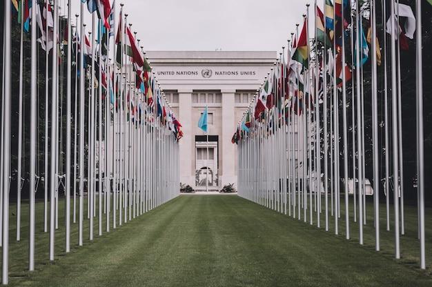 스위스 제네바 - 2017년 7월 1일: 스위스 제네바 유엔 사무소 입구의 국기. 유엔은 1947년 제네바에서 설립되었으며 두 번째로 큰 유엔 사무소입니다.