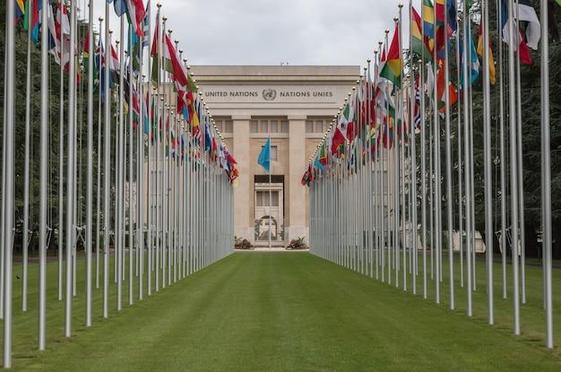 Женева, швейцария - 1 июля 2017 г .: национальные флаги у входа в офис оон в женеве, швейцария. организация объединенных наций была основана в женеве в 1947 году и является вторым по величине представительством оон.