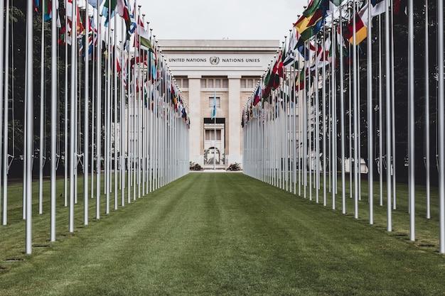 Женева, швейцария - 1 июля 2017 г .: национальные флаги у входа в офис оон в женеве. организация объединенных наций была основана в женеве в 1947 году и является вторым по величине представительством оон.