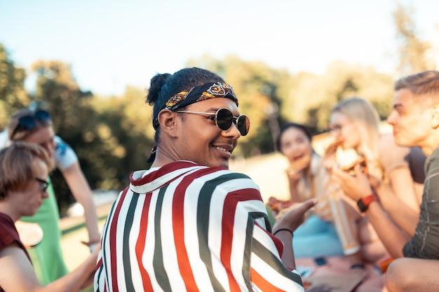 Гениальная компания. улыбающийся мальчик в солнцезащитных очках проводит вечер на пикнике со своими университетскими друзьями.