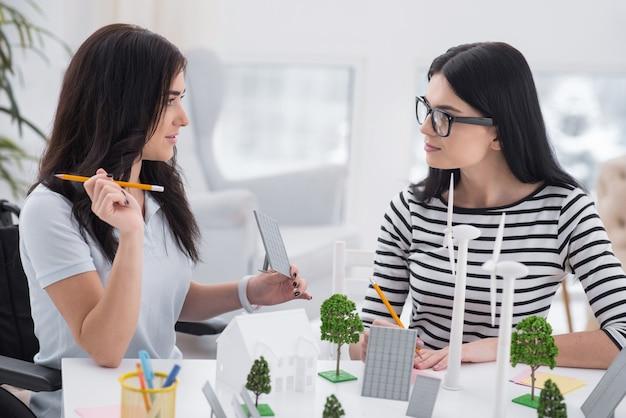 天才ブレインストーミング。障害のある女性と同僚がお互いを見て、代替エネルギーモデルを使って作業している