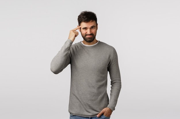 Genius, mindful shopping, good choice. attractive and sassy, confident macho man with beard in grey sweater, tap temple, pointing brain or mind and smiling, thinking, have good idea,
