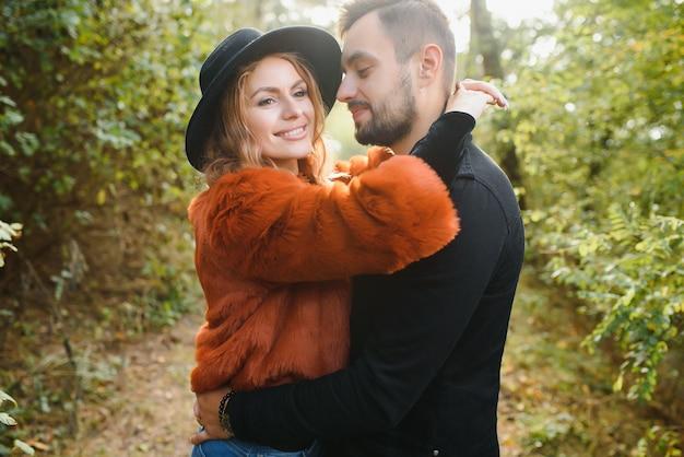優しくてスタイリッシュなカップルが秋の公園を散歩しています