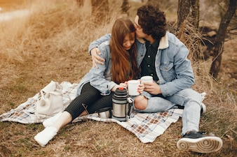 Gentle and stylish couple sitting in the autumn park and drinking a tea