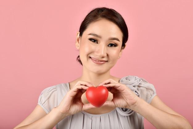 Нежная азиатская женщина держа красное сердце, счастливую усмехаясь женщину показывая знак влюбленности для того чтобы поддержать и ободрить, сердечный осмотр здоровья.