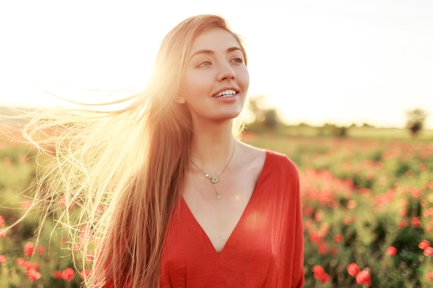 Gentle blonde long-haired woman with perfect smile posing on poppy field in warm summer sunset.