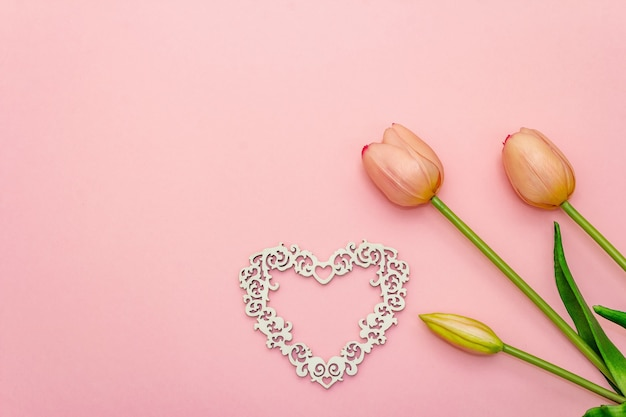 Gentle bouquet of tulips and wooden openwork heart isolated on light pink background. valentine's day or wedding romantic concept, copy space, flat lay, top view