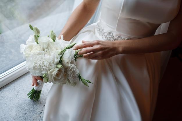 白いバラの優しい花嫁の花束。カーネーションの優しいウェディングブーケをクローズアップ。若い女性の手に白い花の花束。美しくスタイリッシュな花の組成。