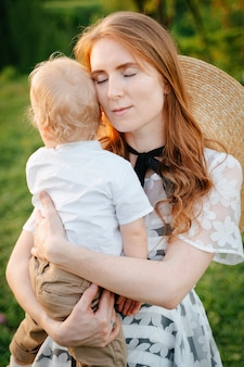 A gentle calm redhaired mother with a child soothes and hugs her sons boy in her arms mothers day