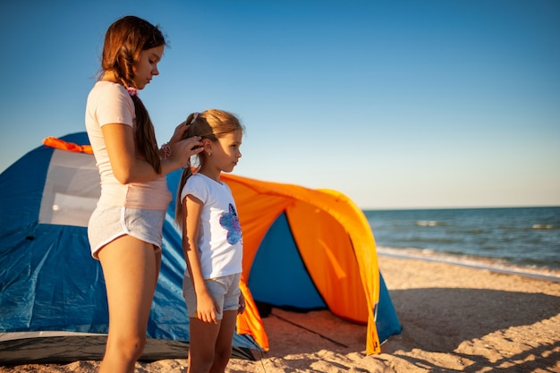Gentle care for loved ones and younger ones girls on the deserted coast of the warm beautiful sea on a beautiful evening