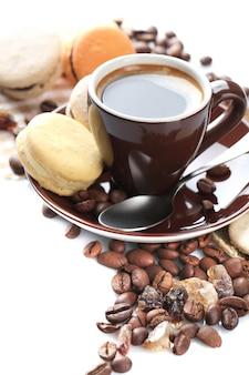 白地に分離されたマグカップの優しいカラフルなマカロンとブラックコーヒー