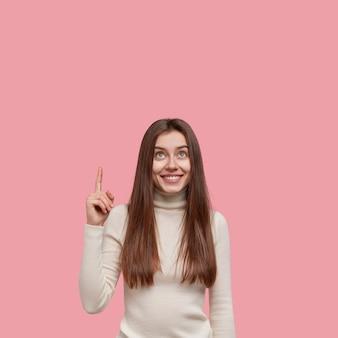 Нежная милая молодая женщина с длинными темными волосами, указательными пальцами вверх, смотрит в потолок, одетая в повседневную одежду