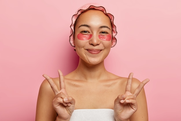 Gentle eastern lady gestures with both hands, shows peace sign, takes care of skin with under eye patches, wears shower cap to protect hair from becoming wet, wrapped in white towel. cosmetology