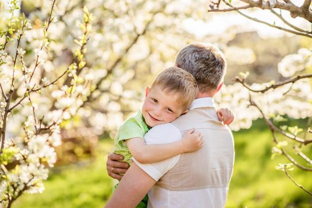 공원에서 아버지와 아들의 부드러운 포옹. 남성 성 개념. 가족 사랑