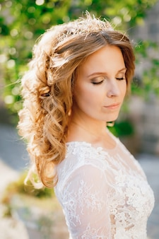 A gentle fairhaired bride in a wedding tiara stands with her eyes closed in the sunlight