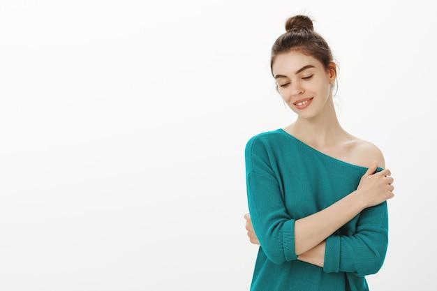 Нежная женская женщина смотрит вниз кокетливо и трогательно плечо