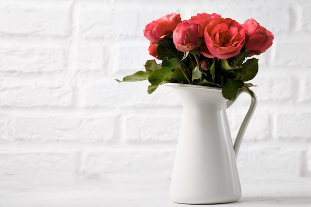 Gentle flowers in white pitcher