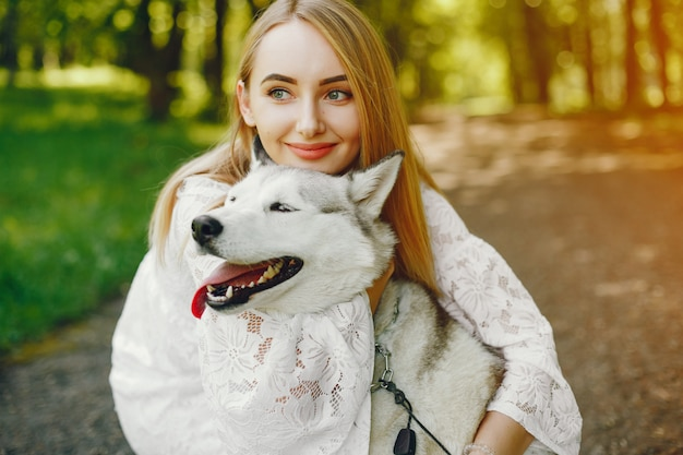 Gentle girl with light hair dressed in white dress is playing along with her dog