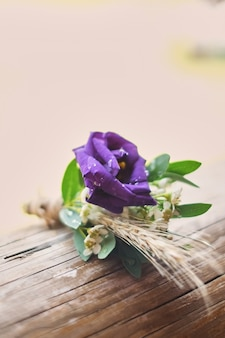 Gentle groom's boutonniere purple lies on a wooden light background