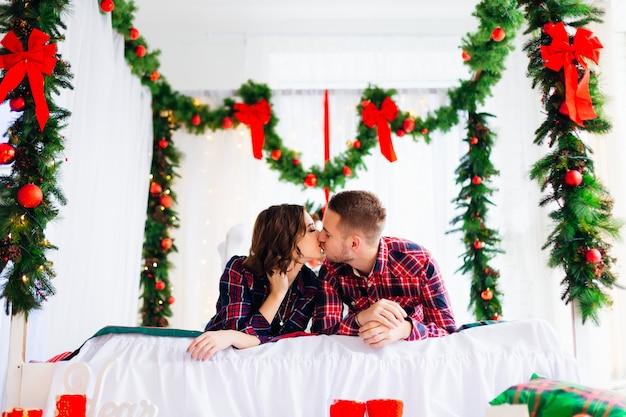 Нежный поцелуй влюбленной пары на кровати, украшенной елочными игрушками
