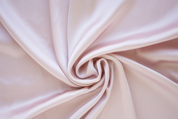 Gentle pastel pink colored satin folded and flowing background decoration design soft focus luxury fashion and femininity concept rose silk backdrop with curves