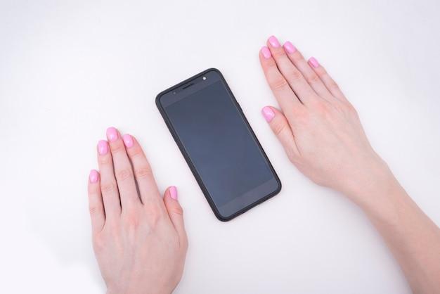 Нежный розовый маникюр. женские руки со смартфоном