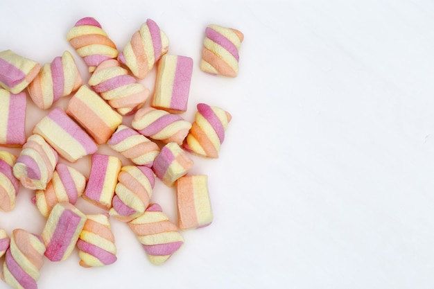 Gentle pink and yellow color marshmallows on white background with copy space. sweet food. pastel color.