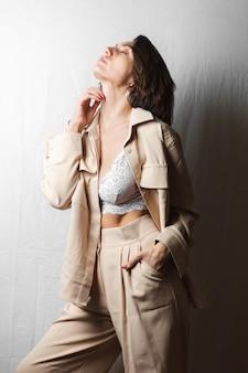 Нежный портрет красивой молодой женщины с большой грудью в бежевом костюме и белом кружевном бюстгальтере на сером белом