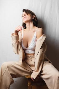 Нежный портрет красивой молодой женщины с большой грудью в бежевом костюме и белом кружевном бюстгальтере сидит на стуле на серо-белом