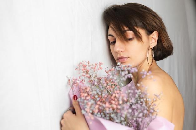 Нежный портрет молодой женщины на белой тряпке топлес, держащей букет сухих разноцветных цветов и милой улыбающейся, предвкушение весны