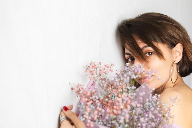 乾いた色とりどりの花の花束を持って、かわいい笑顔、春を期待してトップレスの白いぼろきれの若い女性の優しい肖像画
