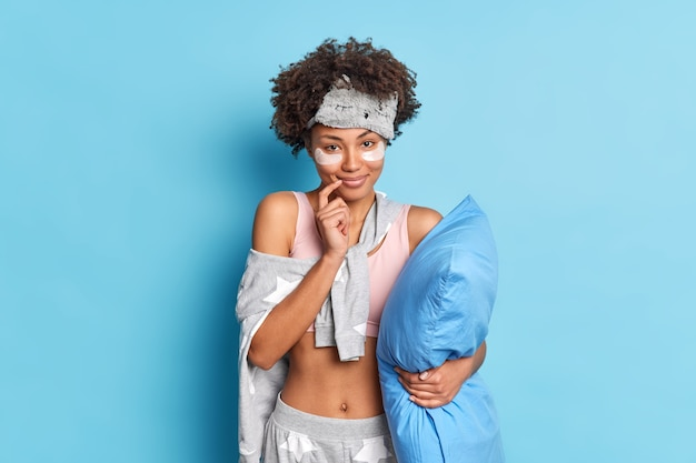 Gentle pretty woman smiles tenderly keeps finger near lips dresed in nightwear holds soft pillow under arm isolated over blue wall applies collagen patches