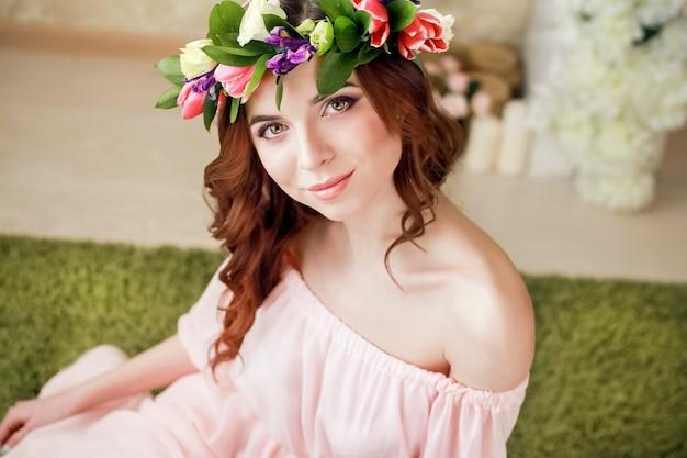 그녀의 머리에 장미 화환과 핑크 드레스와 소녀의 부드러운 낭만적인 모습. 즐거운 졸리 봄 여자입니다. 긴 핑크 드레스에 여름 아가씨